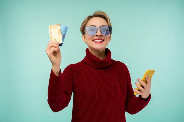 Foto de mulher jovem satisfeita posando isolada sobre o fundo da parede azul, usando o telefone móvel, segurando o cartão de débito.