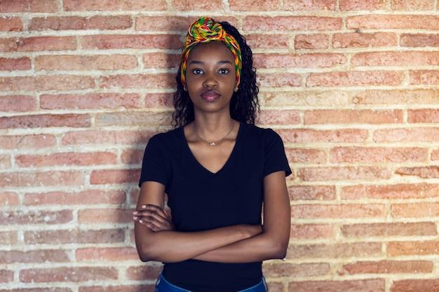 Foto de mulher jovem séria olhando para a câmera com os braços cruzados em frente a uma parede.