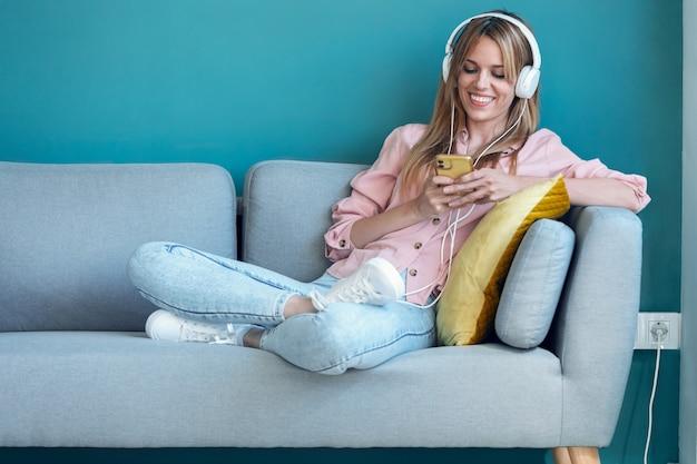 Foto de mulher jovem sorridente ouvindo música com o smartphone enquanto está sentado no sofá em casa.