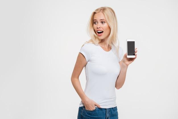 Foto de mulher loira bonita com a boca aberta e mão no bolso, mostrando a tela do smartphone em branco