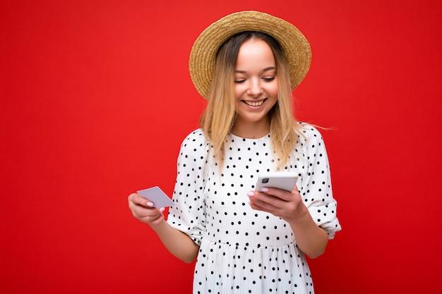 Foto de mulher loira bonita e alegre com roupa de verão, usando telefone celular e segurando um cartão de crédito