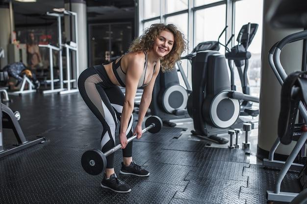 Foto de mulher loira e treinador esportivo, fazendo agachamentos com barra na academia perto de simuladores