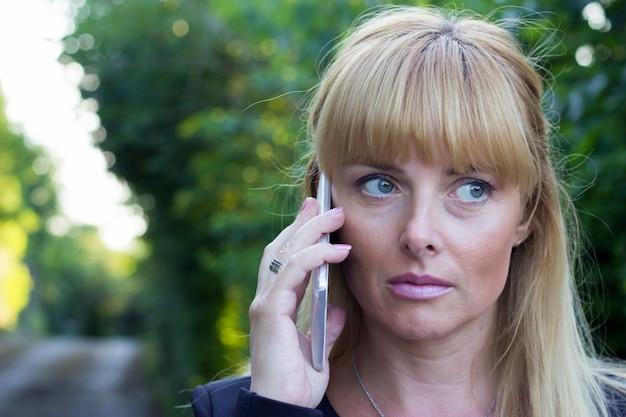 Foto, de, mulher madura, usando, telefone móvel, ao ar livre, durante, dia outono, com, natureza, como, fundo