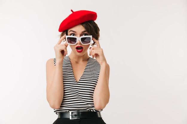 Foto de mulher magnífica com cabelo escuro curto, usando boina vermelha na moda e óculos de sol vintage, isolado sobre o branco