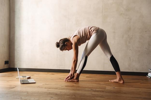 Foto de mulher magra focada em roupas esportivas, alongando o corpo e fazendo exercícios de ioga em casa