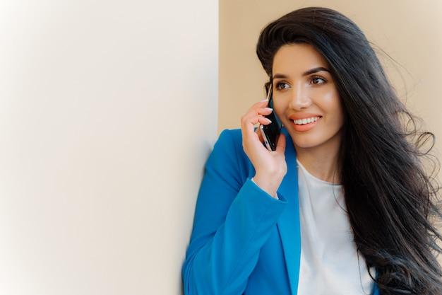 Foto de mulher morena com aparência agradável, cabelos luxuosos, fala no celular