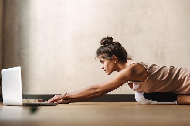 Foto de mulher morena concentrada em roupas esportivas fazendo exercícios de ioga usando laptop enquanto está sentada no chão em casa