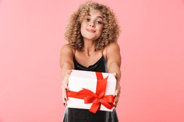Foto de mulher morena encaracolada de 20 anos usando um vestido segurando uma caixa de presente em pé