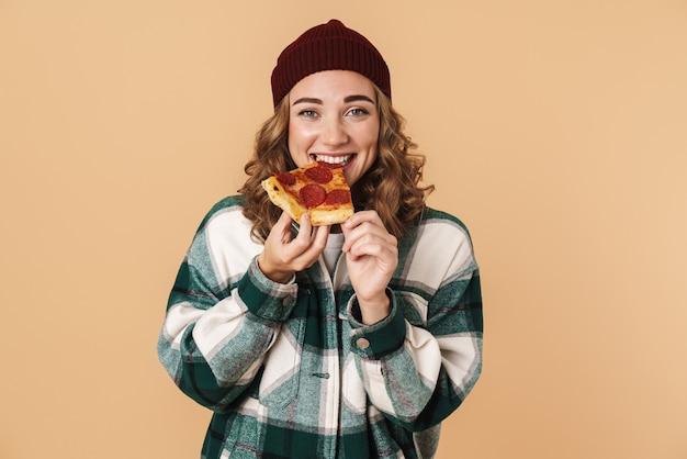 Foto de mulher muito feliz com chapéu de malha sorrindo e comendo pizza isolada em bege