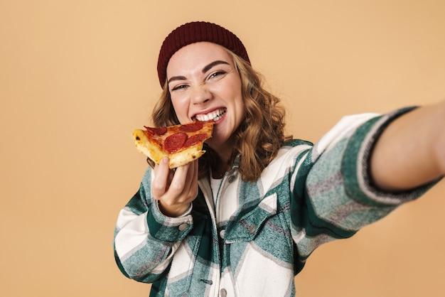 Foto de mulher muito feliz com chapéu de malha tomando selfie e comendo pizza isolada em bege