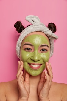 Foto de mulher muito natural tocando as bochechas, sorri suavemente e aplica máscara de beleza no rosto, cuidados com a pele e o corpo fica nu em casa segue o conselho do cosmetologista sobre como reduzir acnes