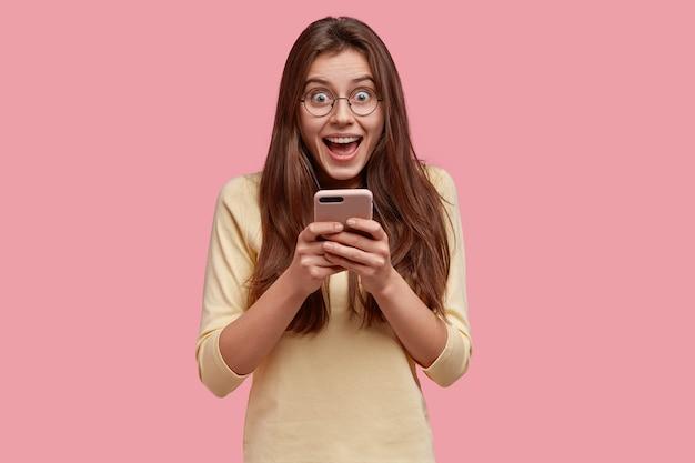 Foto de mulher muito satisfeita segurando o celular na cintura, feliz por trocar mensagens de texto nas redes sociais