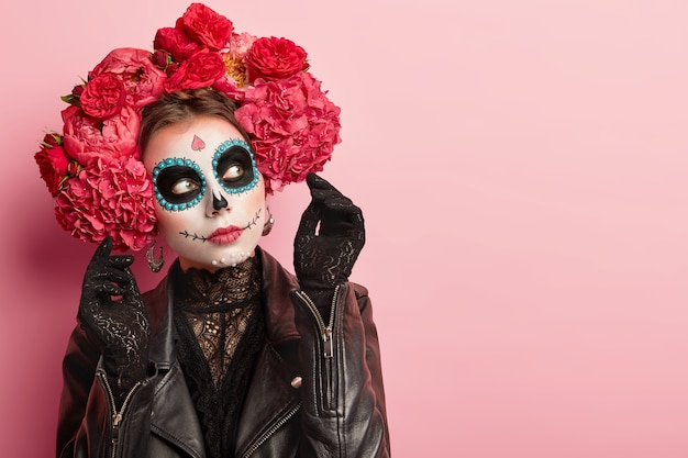 Foto de mulher pensativa com maquiagem de halloween, vestida com roupa tradicional preta