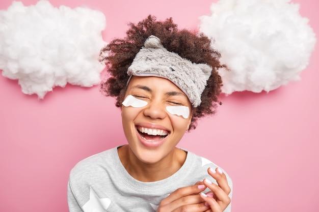 Foto de mulher positiva com cabelo encaracolado fecha os olhos, sorri e mostra os dentes vestidos com pijamas submetidos a tratamentos faciais poses contra a parede rosa