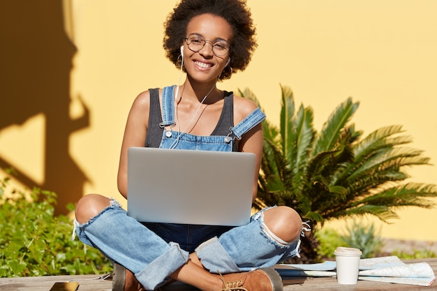 Foto de mulher relaxada e despreocupada de pele escura se senta com as pernas cruzadas, navega no site da internet no computador laptop, desfruta de uma bebida fresca, ouve uma faixa de áudio agradável com fones de ouvido blogueira afro-americana