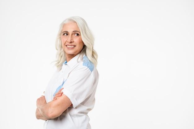 Foto de mulher satisfeita adulta com cabelos grisalhos, sorrindo e olhando de lado no espaço da cópia com as mãos cruzadas, isolado sobre a parede branca
