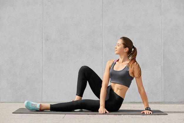 Foto de mulher satisfeita relaxada descansa após treino cardio
