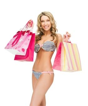 Foto de mulher sedutora de biquíni com sacolas de compras