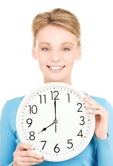 Foto de mulher segurando um grande relógio sobre o branco