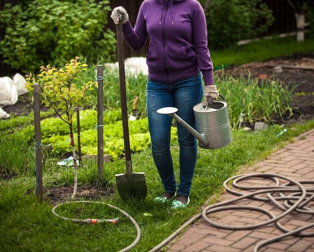 Foto de mulher segurando uma pá e um regador no jardim