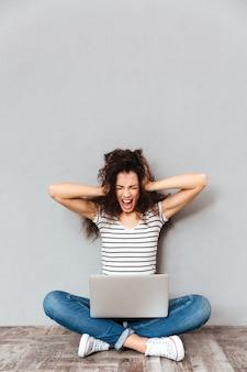Foto de mulher sentada com as pernas cruzadas no chão, gritando e cobrindo as orelhas, decepcionada com os resultados dos exames sobre a parede cinza