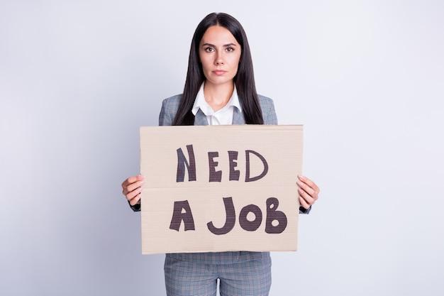 Foto de mulher séria, representante da equipe demitido, pessoa que perde a procura de emprego, mostrando um cartão de papel que precisa trabalhar, usar calças xadrez xadrez isoladas sobre um fundo de cor cinza
