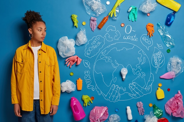 Foto de mulher séria, voluntária focada à parte, sendo ativista ecológica, pensa em como salvar o planeta da poluição do plástico, tem muitos pensamentos, coleta lixo para reciclagem.