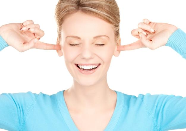 Foto de mulher sorridente com as mãos nas orelhas