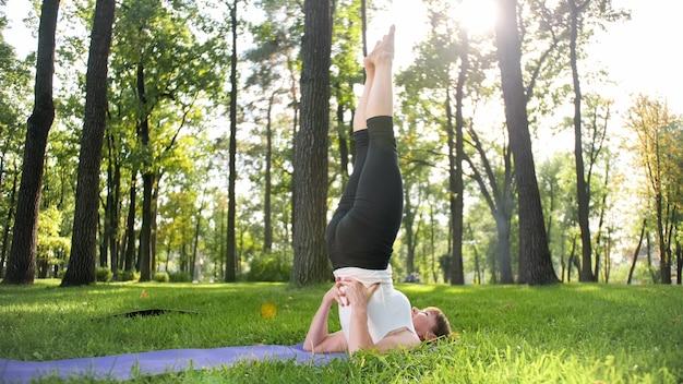 Foto de mulher sorridente de meia idade praticando ioga asana. persiga a meditação na natureza. equilíbrio e harmonia de corpo e mente