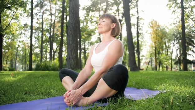 Foto de mulher sorridente de meia idade praticando ioga e meditando no parque. mulher se alongando e se exercitando no tatame na floresta