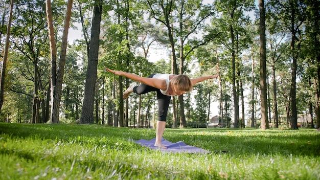 Foto de mulher sorridente, fazendo exercícios de ioga e fitness. pessoas de meia idade cuidando de sua saúde. harmonia de corpo e mente na natureza