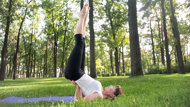 Foto de mulher sorridente feliz de 40 anos fazendo exercícios de ioga na esteira de fitness na floresta. harmonia da natureza humana. pessoas de meia idade cuidando da saúde mental e física