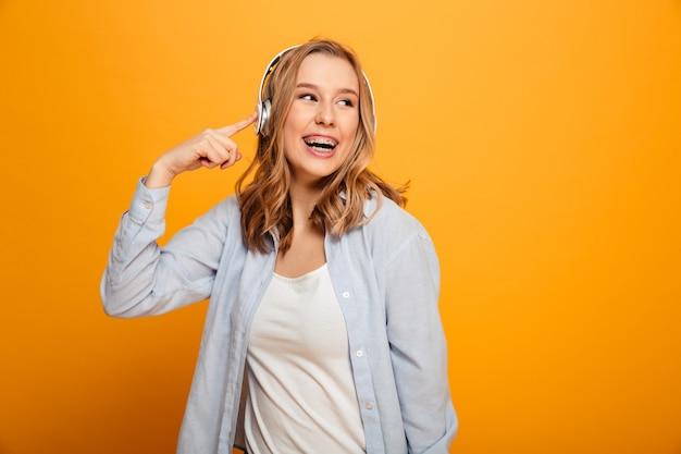 Foto de mulher sorridente satisfeito 20 anos usando aparelho em roupas casuais, ouvindo música usando fones de ouvido sem fio, isolados sobre o espaço amarelo
