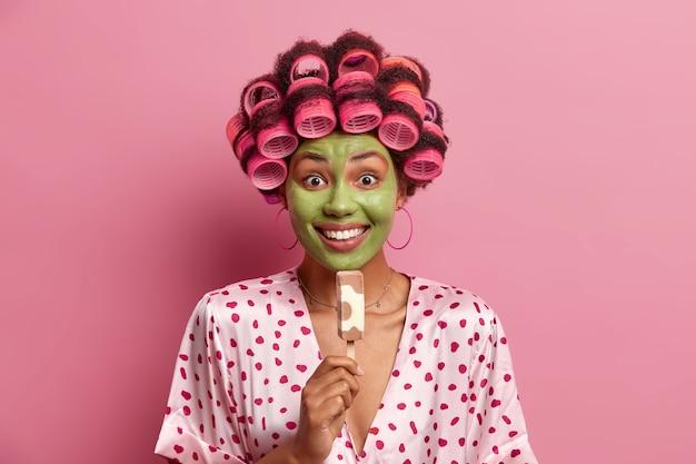 Foto de mulher sorridente sorri amplamente, aplica máscara hidratante verde, come delicioso sorvete no palito, usa rolos de cabelo, roupão de seda, aproveita o horário de verão. dona de casa com sobremesa gelada