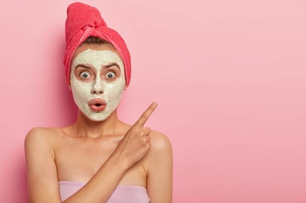 Foto de mulher surpresa e muda usando máscara facial, tem procedimentos de beleza em casa, expressão chocada, aponta para o lado com o dedo indicador, toalha enrolada no cabelo molhado