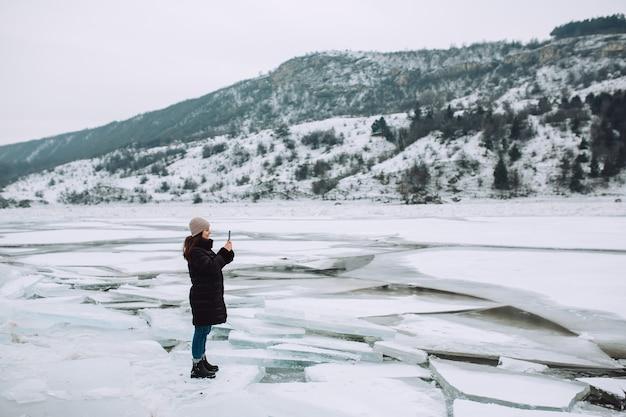 Foto de mulher tirada com seu smartphone na paisagem de inverno com blocos de gelo e colina nevada.