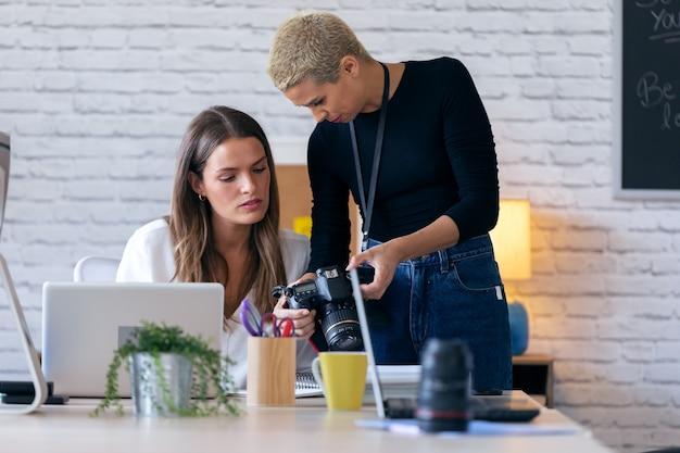 Foto de mulheres empresárias modernas revisando as últimas fotos na câmera para o próximo trabalho no escritório.