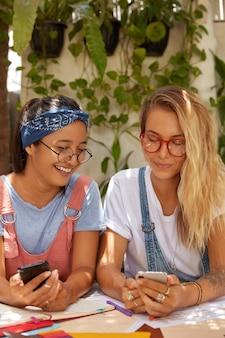 Foto de mulheres multiétnicas compartilhando arquivos multimídia via bluetooth, segurando celulares modernos, sentando na mesa, colaborando para tarefas comuns, usando óculos transparentes, sendo viciadas em tecnologias modernas