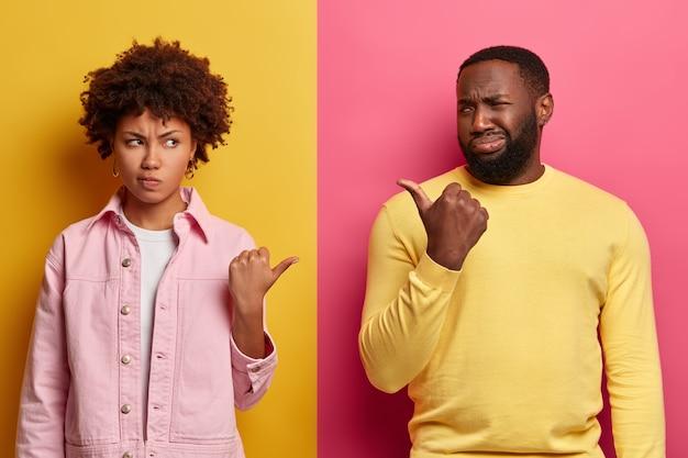 Foto de namorada e namorado cacheados étnicos pessimistas descontentes apontando o polegar um para o outro e sorrindo com tristeza