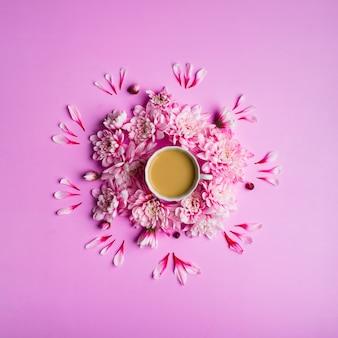 Foto de natureza morta de café com leite em uma xícara com flores de crisântemo ao redor