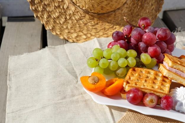 Foto de natureza morta e comida piquenique na natureza em dia ensolarado chapéu de palha e prato de frutas vermelhas e waffles ficam em tecido de serapilheira no chão de madeira de tábuas velhas