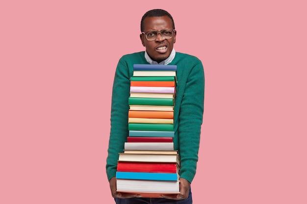 Foto de nerd descontente aperta os dentes, segura uma pilha de livros, usa óculos grandes e suéter verde