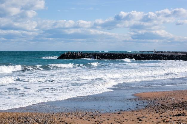 Foto de ondas relaxantes do mar na costa com doca de pedra sob céu nublado