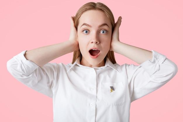 Foto de orelhas de plugues femininas irritadas ao ouvir música alta, chocou a expressão, olhos azuis e pele saudável e macia, veste blusa branca, isolada na parede rosa pessoas e expressões faciais