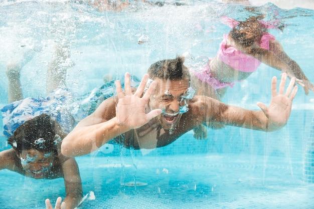 Foto de pai de família feliz com filhos mergulhando e nadando debaixo d'água na piscina, durante as férias de verão