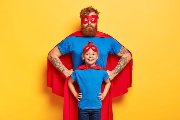 Foto de pai e filha ruivos confiantes mantendo as mãos na cintura