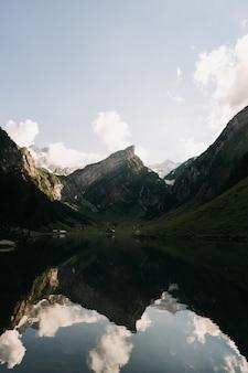 Foto de paisagem de montanhas e colinas com seus reflexos mostrados em um lago sob um céu claro