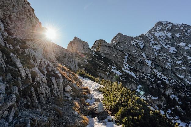 Foto de paisagem de montanhas nevadas com o sol brilhando