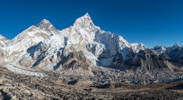 Foto de paisagem de um belo vale cercado por enormes montanhas com picos nevados