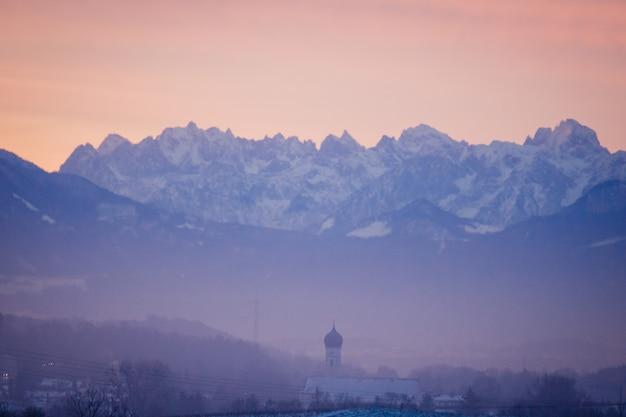Foto de paisagem de um cenário roxo com o céu laranja da montanha ao fundo
